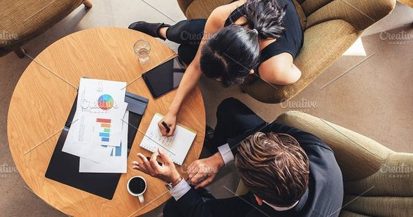 View from above of two business people planning work around table. Businessman and woman going through the to do list while sitting at office lobby.