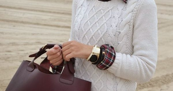 White cable knit sweater, red plaid button down shirt, brown bag, and
