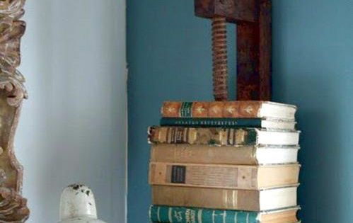 Vintage old wood vise tool repurposed into a wall book holder shelf.