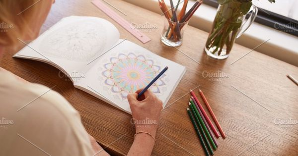 Woman relaxing at home and drawing in colouring book for adults. Woman coloring designs with color pencils for relaxation at home.