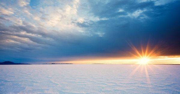 A rising sun illuminates the crystalline salt patterns of Utah's Bonneville Salt