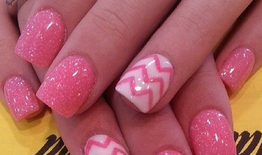 Pink glitter nails with an accent chevron nail.