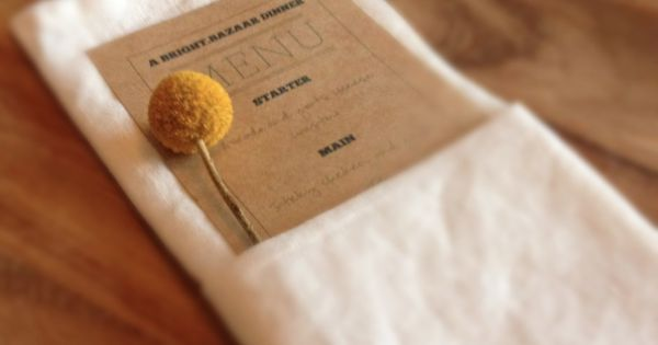 Place setting with craspedia, kraft paper menu, linen napkin and acacia wood