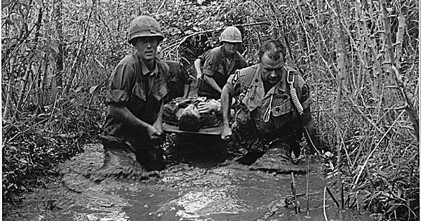 soldiers carry  wounded comrade   swampy area     national archives