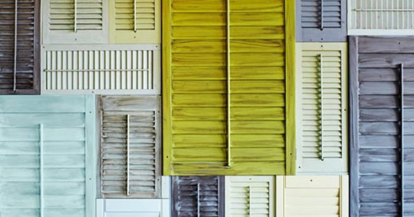A wall collage made of old shutters painted acid yellow, dusty grey