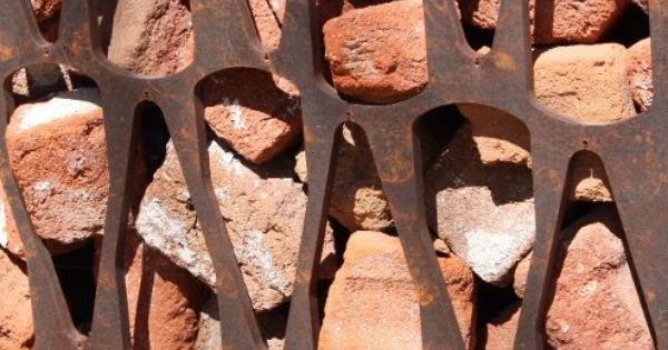 this is a huge twist on gabion. recycled broken brick, corten patterned