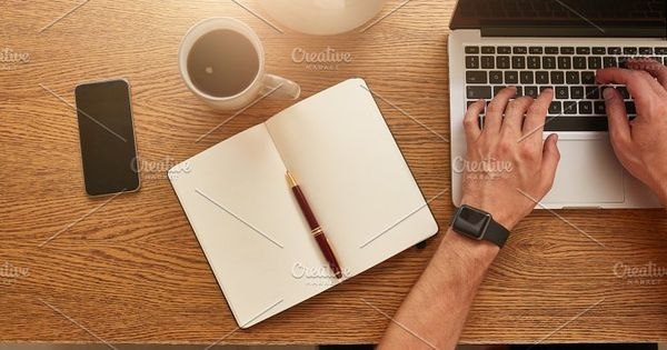 Top view of businessman working at his desk. Modern workplace with laptop, smartphone, diary and coffee cup.