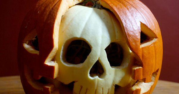 Halloween Pumpkin carving, white pumpkin skull inside orange pumpkin jack o lantern