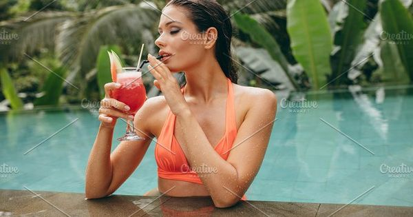 Portrait of young woman drinking cocktail while standing in swimming pool. Caucasian female model in bikini at luxury holiday resort.
