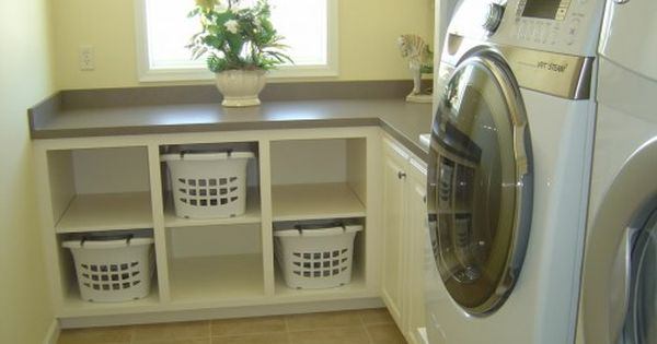 Dream Laundry Room idea: Folding counter with space for everyone's basket of