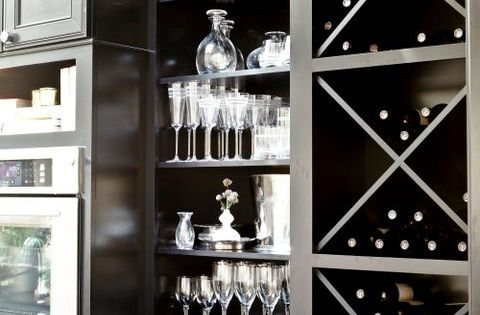 Suzie: Grothouse Lumber - Glossy black cabinets with built-in wine racks and