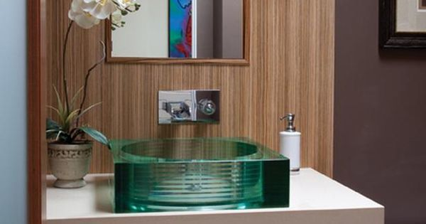A polished-glass vessel sink sits atop the upper vanity ...