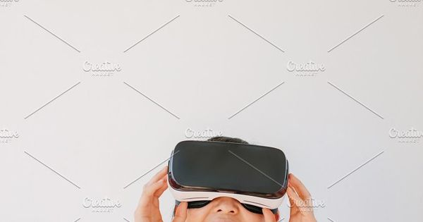 Vertical shot of woman using the virtual reality headset and smiling against grey background. Happy female model wearing VR goggles.