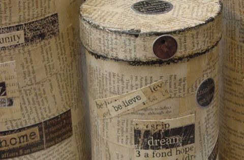 Decoupage oatmeal canisters with old book pages to make supply containers for