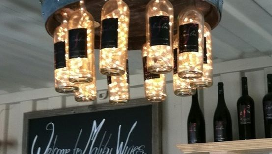 Chandelier made with a wine barrel, empty wine bottles and strands of