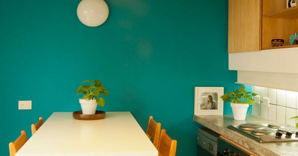 Kitchen With Teal Turquoise Wall Paint And Wood Cupboard Fronts