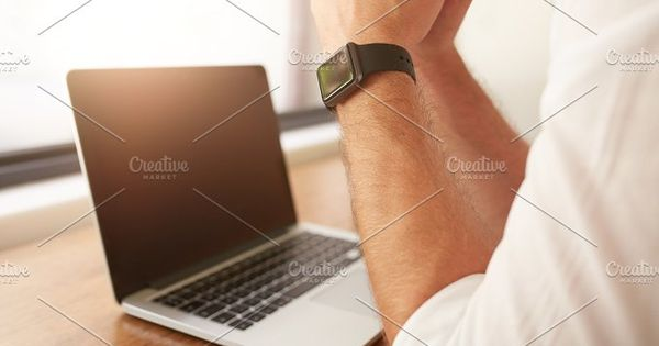 Close up of man sitting at his desk with laptop, he is wearing a smartwatch.