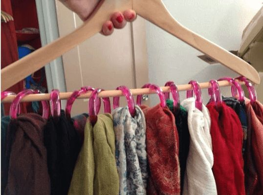 It takes a little ingenuity to make space in a tight closet. Take this super idea, for example. All you need is a dozen or so shower hooks, a wooden or metal hanger, then organize your scarves as shown in the image below. This idea also works for tank tops, belts and more.