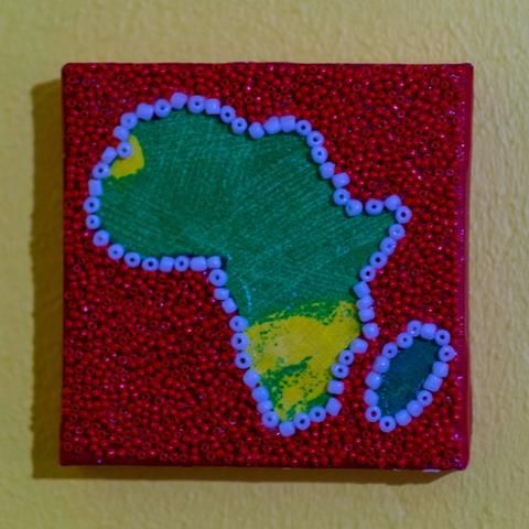 Shop: Canvas D'Afrique - Red. This Africa is partially beaded on canvas in red and light blue with a center of fgreen and yellow fabric. Size: 10cm x 10cm. By Boudoir D'Afrique