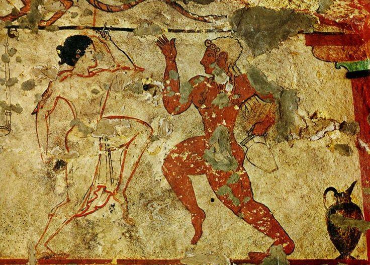 Tarquinia, Tomba delle Leonesse (520 a.C.). Una coppia di danzatori. La donna ha la gamba sinistra sollevata, mentre nella mano destra, abbassata, tiene delle nacchere di colore nero. Indossa una veste trasparente bordata di rosso che sottolinea le linee del corpo. A lei è contrapposto un danzatore dalla fluente capigliatura che stringe un recipiente di vino nella sinistra.