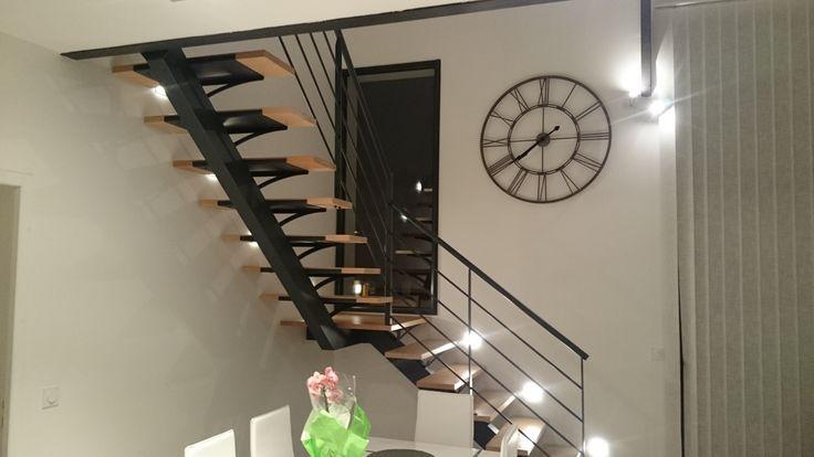 Escalier 1/4 tournant limon central, marches sans contremarches. Limon métallique epoxy noir avec marches en bois. Garde corps métallique avec verre stadip sous pinces inox. www.escaliershaquette.com