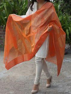 White Chudidar and kurta with a beautiful orange dupatta.