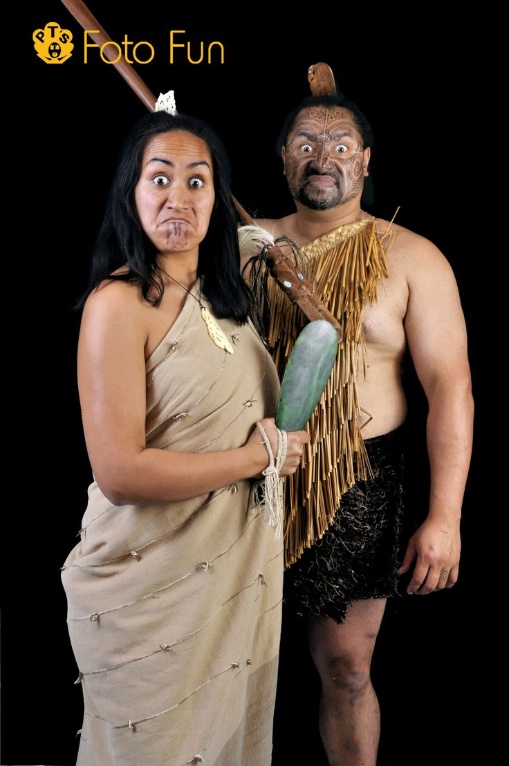 Maori couple with weapons in traditional pose and outfits