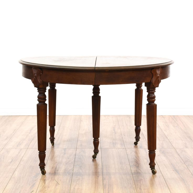 This victorian dining table is featured in a solid wood with a glossy cherry finish and distressed table top. This dining table has carved spindle legs, caster wheel feet and 3 large leaves. Perfect for entertaining in a large dining space! #countryfarmhouse #tables #diningtable #sandiegovintage #vintagefurniture
