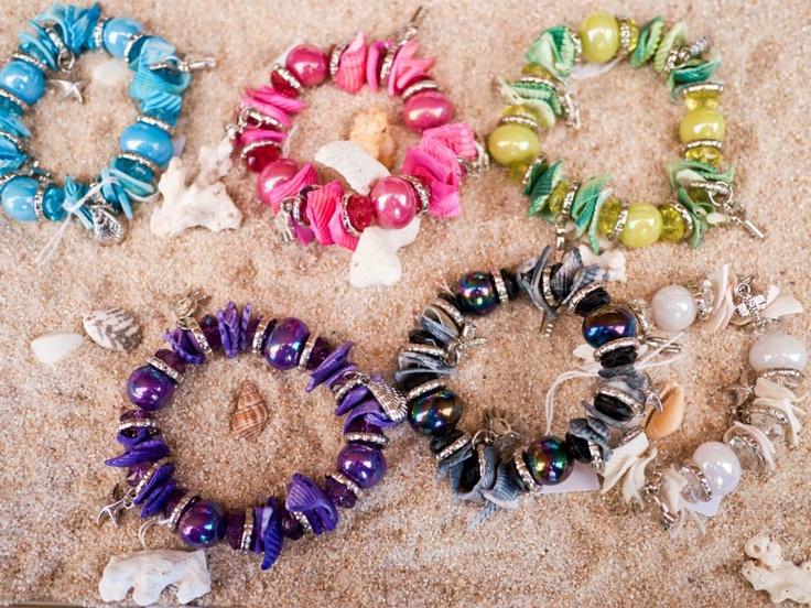 Pulseras elásticas de conchas naturales tintadas, bolas nacaradas y varios colgantes color plata.