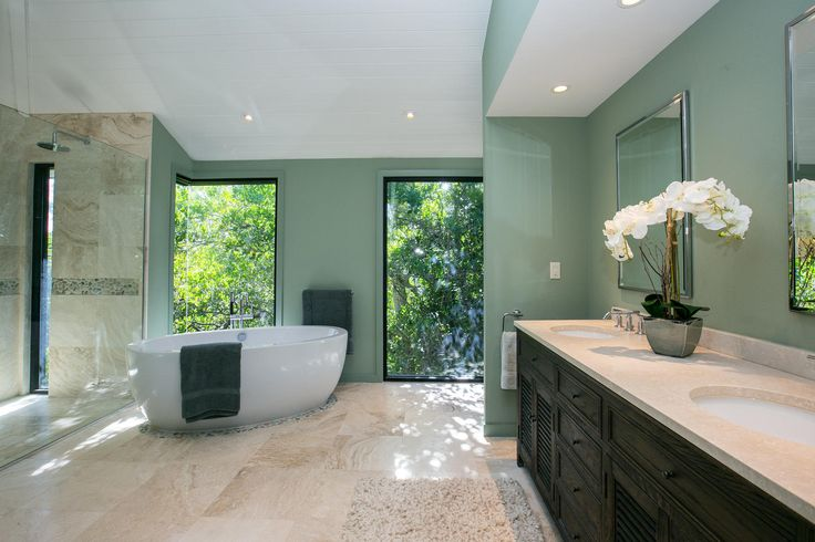 Luxury Bathroom  - mint green with light pouring through the full length windows. Orchids scenting this magical space. The perfect bathroom decor for a luxury beach side soak.