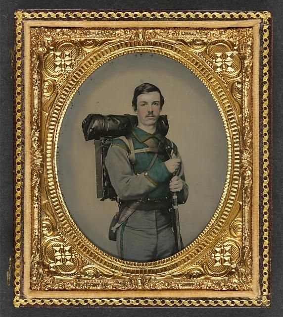 "Photograph shows a soldier in 1861 in a Confederate uniform of Company E, ""Lynchburg Rifles,"" 11th Virginia Infantry Volunteers holding 1841 ""Mississippi"" rifle, Sheffield-type Bowie knife, canteen, box knapsack, blanket roll, and cartridge box."