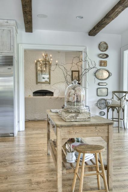 white painted brick fireplace +  silver trays on the wall +  branches