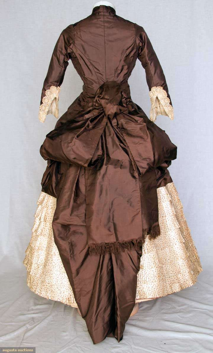 Two tone silk bustle dress (Back), c. 1880. Chocolate brown polonaise bodice extends to side draped & back bustle over-skirt, 10 crochet ball buttons, cream silk twill skirt w/ tiny brown flower head print, skirt has CB square insert of solid brown & bustle ties, embroidered lace cuffs, tan cotton lining.