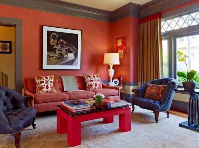 decoración clásica con paredes rojas, salón con ventanas grandes y cortinas masivas, mesa roja con revistas, flores, sillónes tapizados en capitoné azules