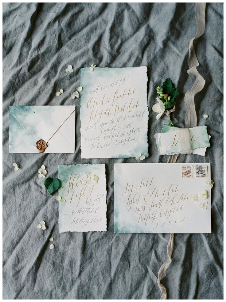 Exquisite wedding invitation suite on blue watercolor deckle edge paper with a gold wax seal and gold and gray calligraphy by Graceline Art. Image by Shannon Moffit.