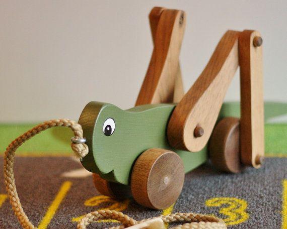 Der Grasshopper-Körper ist mit ungiftiger Acrylfarbe handgemalt. Die Beine und Räder sind gefärbt. Die Fertigkeit-Garn-Schleppleine wird an einem Auge Haken angebracht, die geklebt ist. Wie das Spielzeug gezogen wird gehen die gelenkartigen Beine abwechselnd rauf und runter.  Dieses Spielzeug ist auf Lager und versandbereit. Die Abmessungen sind: 12½ L x 6 H X 4 W.  Vielleicht bevorzugen Sie die Lime Green Grasshopper: https://www.etsy.com/listing/105364108/grasshoppe...