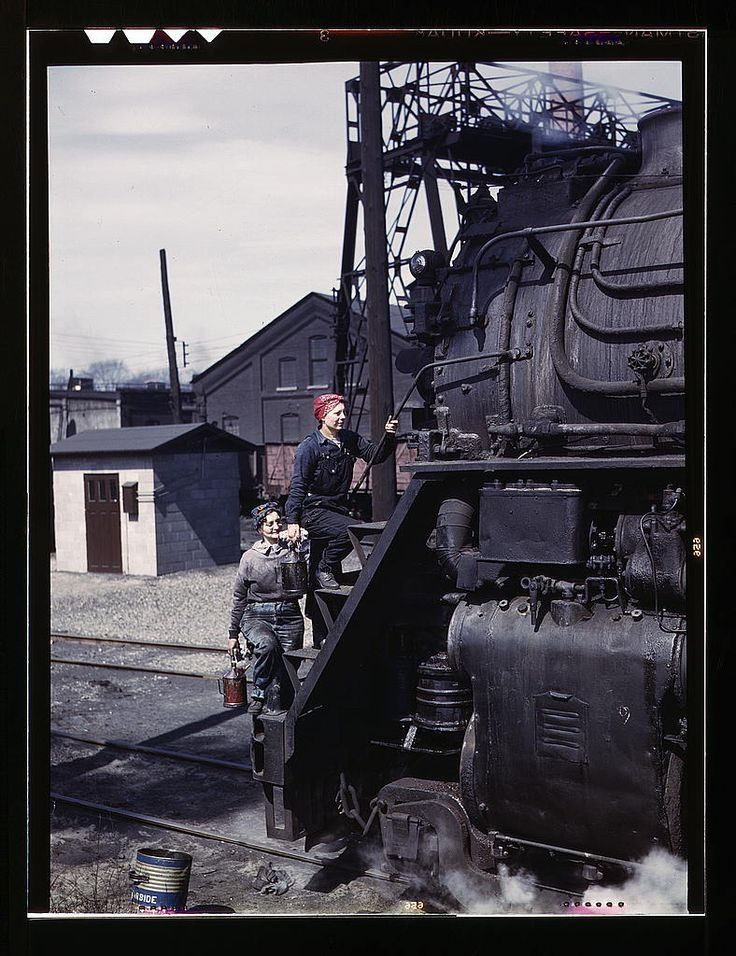 """Women wipers of the Chicago and North Western Railroad cleaning one of the giant """"H"""" class locomotives, Clinton, Iowa. Mrs. Marcella Hart and Mrs. Viola Sievers. Delano, Jack,, photographer."""