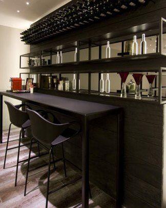 Um ambiente com atmosfera de bar, a partir de uma composição da Estante Modena, que possui um requadro de alumínio e bases em vidro, e as Cadeiras Nina Bar, com design suíço e uma altura diferenciada, indicada para bancadas.