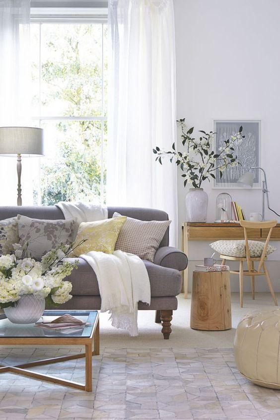 Szara sofa w pastelowym salonie