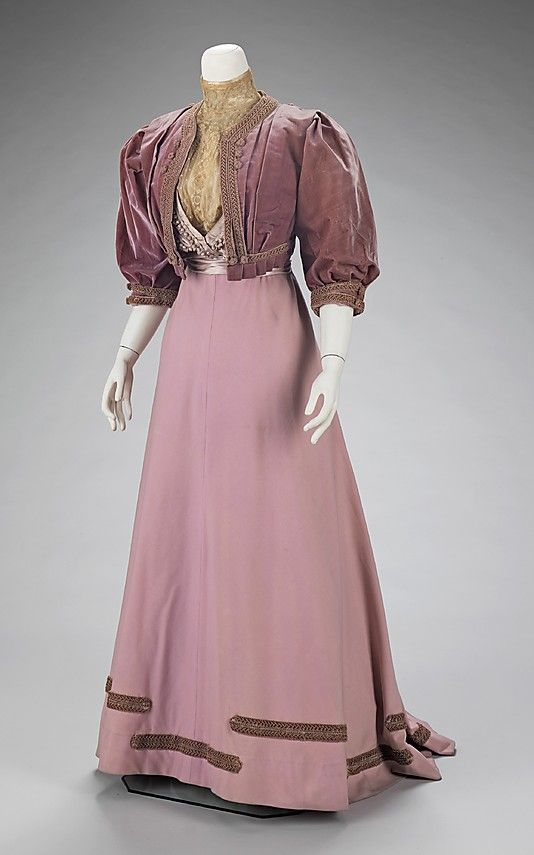 Mauve silk and wool afternoon suit (with velvet jacket), by Jeanne Paquin, French, 1906-08. This dress highlights Paquin's technique to create interesting light and textural effects. Four kinds of decorative materials- box-pleated ruching, silk-wound beads, point d'esprit and patterned net lace - each with its own reflective textural quality, are combined on the bodice. The silk-wound beads, attached only at one end for maximum protrusion, add a contrasting shape and a glittering effect.