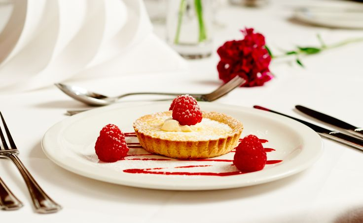 Individual lemon tart served with raspberries and clotted cream