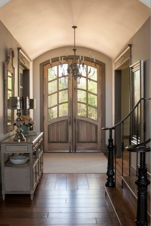 Bright entry in weathered gray with arched ceiling and doors. #entryways #foyers homechanneltv.com