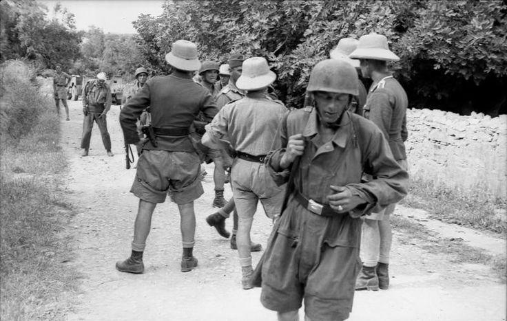 Η ΑΝΤΙΣΤΡΟΦΗ ΜΕΤΡΗΣΗ άρχισε ήδη... Αξιωματικοί και στρατιώτες κινούνται για να πάρουν θέσεις γύρω από τους προς εκτέλεση συγκεντρωμένους. Ένας τραυματίας στο βάθος φαίνεται για την ώρα να έχει απομακρυνθεί από τους μελλοθάνατους, ενώ ο δρόμος έχει ερημώσει από τα γυναικόπαιδα και τους γέροντες... Η φωτογραφία αυτή είναι ο πρόλογος του ολοκαυτώματος