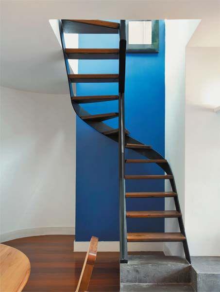 O pilar central, fixado na base de alvenaria e em uma viga de concreto da cobertura, sustenta a escada metálica. Para reforçar a estrutura, o segundo pilar, de desenho sinuoso, foi aparafusado na parede azul. Os degraus de ipê têm 20 cm de profundidade máxima e o vão entre eles, 18 cm de altura.