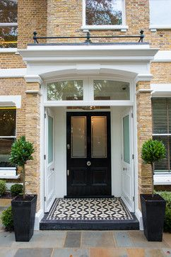 Stunning black and white tiled porch with bay trees and complimentary planters. Tasteful. Cleeves House - traditional - Entry - London - Alexander James Interiors