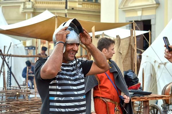 A swarthy man with rather bad teeth trying with great amusement a medieval iron helmet at the medieval Festival in Sibiu, Transylvania, Romania, August, 2013.