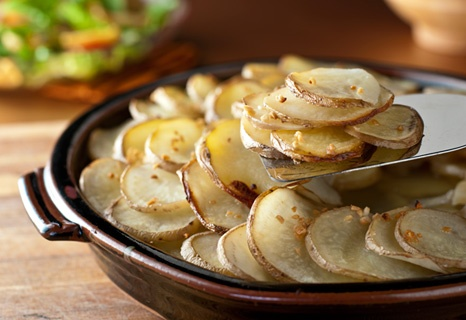 Sliced Potatoes Are Roasted In A Combination Of Chicken Broth And Minced Garlic Resulting In A