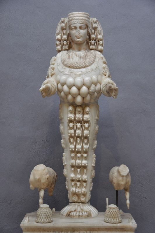 """The second statue (id. no. 718) known as """"the beautiful Artemis"""" dates to the second cent. AD. The headdress is missing on this statue but she does retain both of her hands. She is standing between a deer and a beehive. The necklace is encrusted with the signs of the Zodiac."""