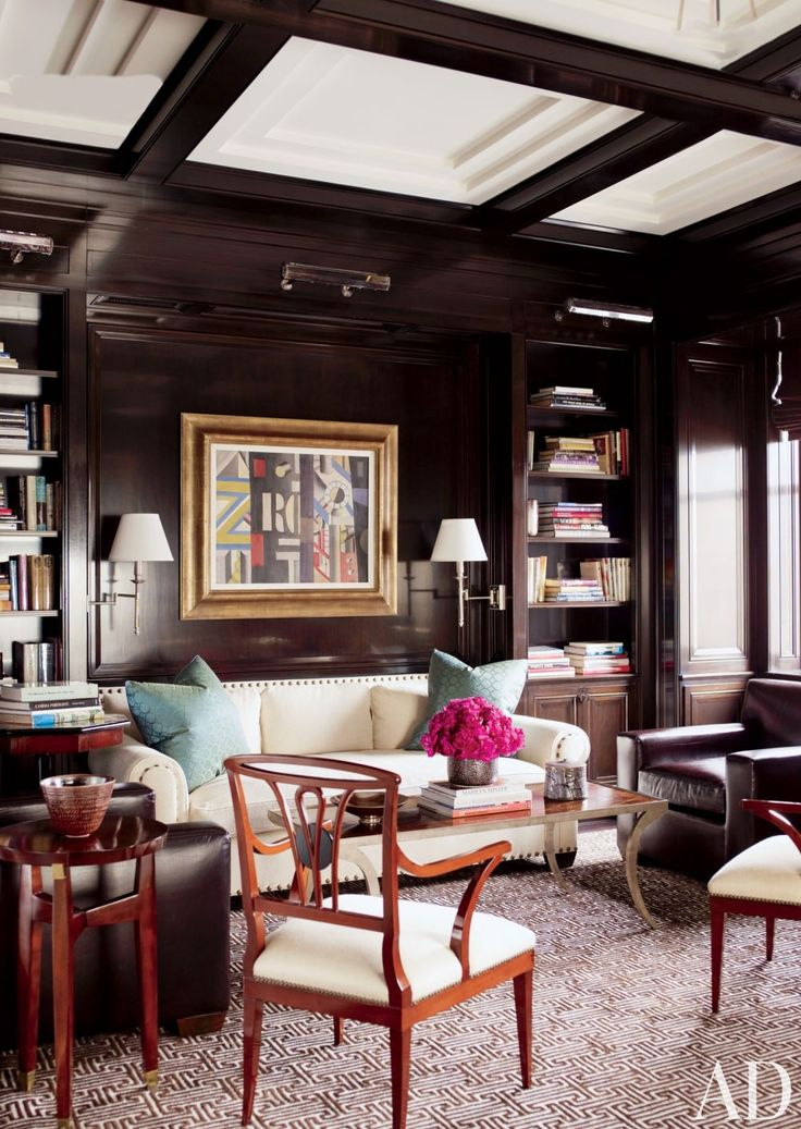 The mahogany-paneled library of a New York City home features antique armchairs and a painting by Fernand Lèger