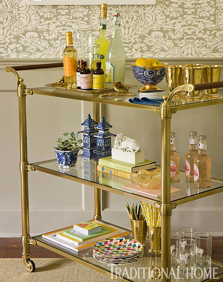 Bar carts can go above and beyond when entertaining, holding everything from beverages and plates to artbooks for kids. - Photo: Gordon Beall / Design: Marika Meyer